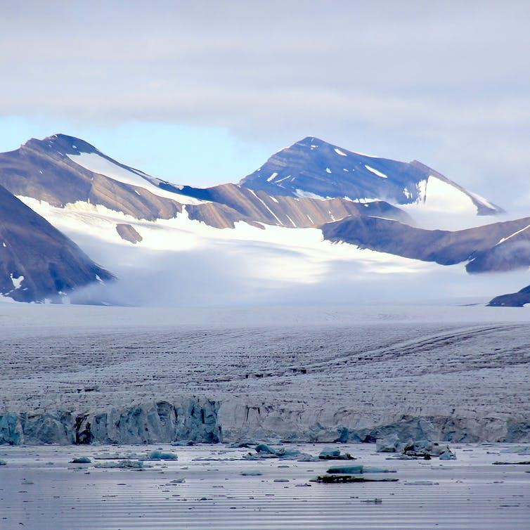 Large glacier flows into the sea. White in background and grey in the foreground.