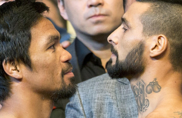 Philippine senator and boxing hero Manny Pacquiao, left, and Argentine WBA welterweight champion Lucas Matthysse gaze at each other after weigh-ins in Kuala Lumpur, Malaysia, Saturday, July 14, 2018. Matthysse and Pacquiao were scheduled to fight on July 15, for the World Boxing Association welterweight title in Malaysia. (AP Photo/Yam G-Jun)