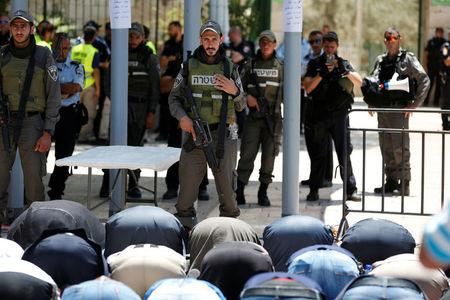Palestinians pray as Israeli police officers look on by newly installed metal detectors at an entrance to the compound known to Muslims as Noble Sanctuary and to Jews as Temple Mount in Jerusalem's Old City July 16, 2017. REUTERS/Ronen Zvulun