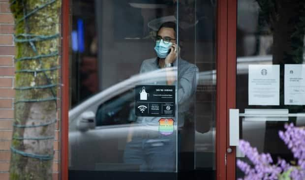 A man in a face mask inside a Starbucks in Vancouver on May 25. British Columbia is again making masks mandatory for indoor public spaces across the province as of Wednesday. (Maggie MacPherson/CBC - image credit)