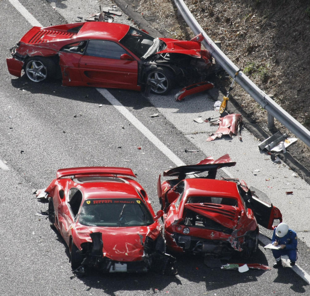 Police officers investigate wrecked luxury cars at the site of a traffic accident on the Chugoku Expressway in Shimonoseki, southwestern Japan in this December 4, 2011 photo taken by Kyodo. Ten people were slightly injured in the pile up involving eight Ferraris, a Lamborghini, two Mercedes-Benz and two Japanese cars, according to the police. A group of luxury sports car fans were believed to be driving together when the accident occurred, local media reported. Picture taken December 4, 2011. Digital masking of license plate from source.  (REUTERS/Kyodo)
