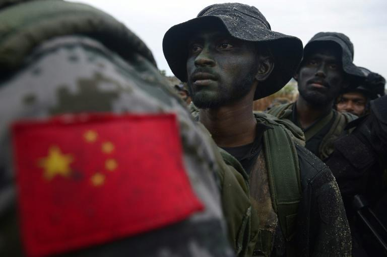 A Chinese soldier stands with Sri Lankan military personnel during a training exercise on the eastern coast of Trincomalee in September 2019