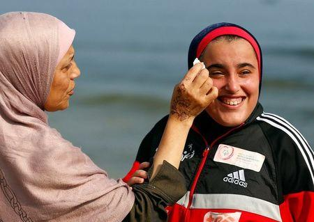 The mother of Special Olympics athlete Esraa Gamal cleans her face on a beach in Alexandria, Egypt, July 18, 2017. REUTERS/Mohamed Abd El Ghany