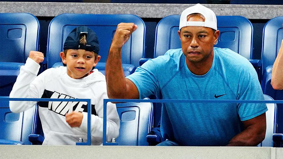 Tiger Woods and his son Charlie (pictured) cheer on.