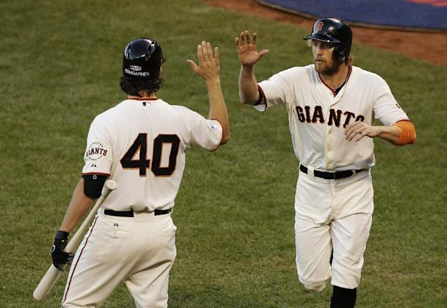 San Francisco Giants Hunter Pence, right, is congratulated by Madison Bumgarner after scoring on a ground out by Brandon Crawford during the second inning of Game 5 of baseball's World Series against the Kansas City Royals Sunday, Oct. 26, 2014, in San Francisco. (AP Photo/Jeff Chiu)
