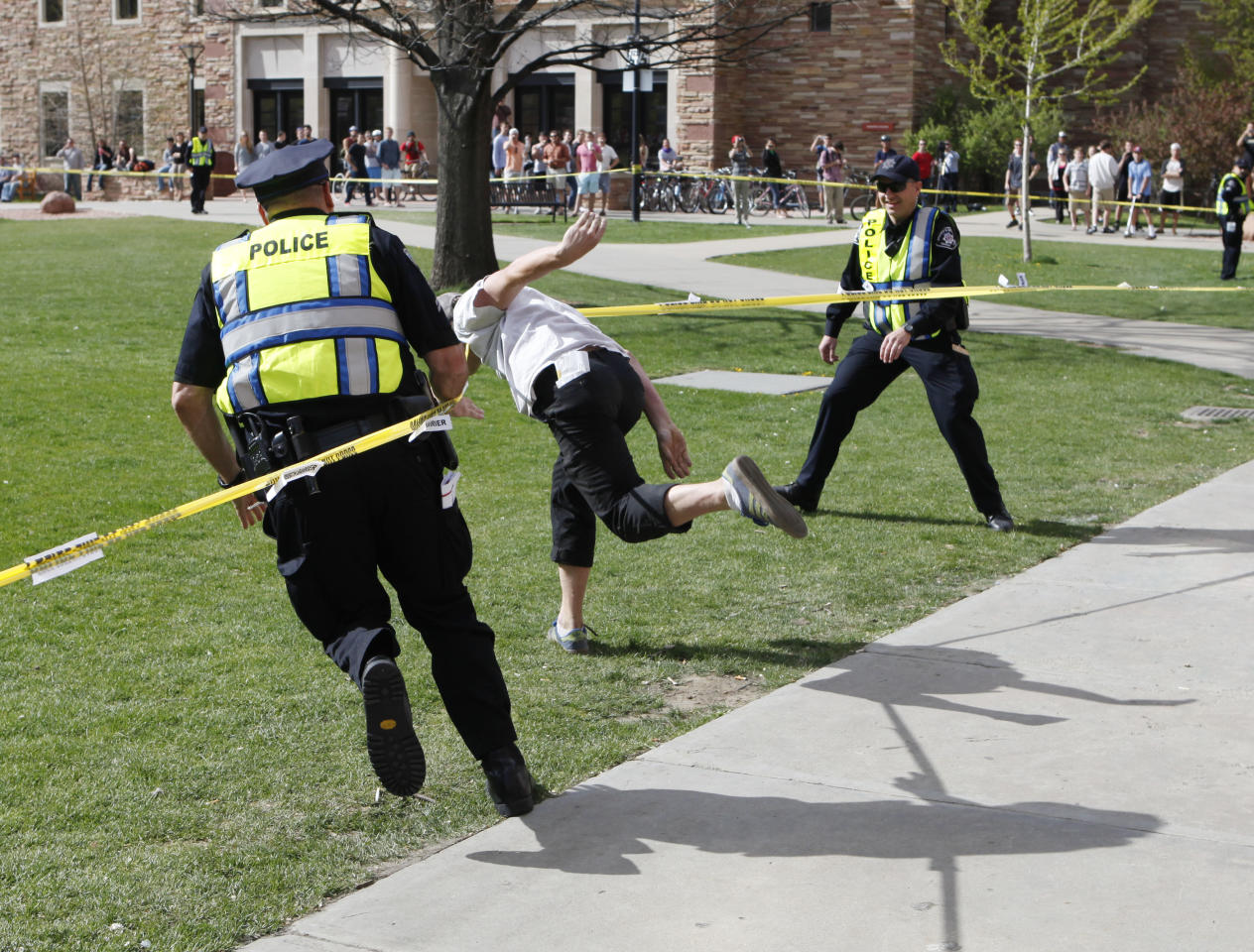 Police try to stop a student as he runs through the police barrier on the Norlin Quad at the University of Colorado in Boulder, Colo., on Friday, April 20, 2012, at 4:20pm. He was run down by police and arrested after crossing the barrier. Police blocked off the quad to prevent a 420 marijuana smoke out. (AP Photo/Ed Andrieski)