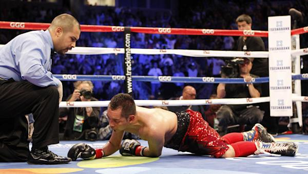 Referee Raul Caiz Jr., left, watches Nonito Donaire on the canvas after Donaire lost to Nicholas Walters in the sixth round during a WBA featherweight title boxing fight, Saturday, Oct. 18, 2014, in Carson, Calif. (AP Photo/Alex Gallardo)