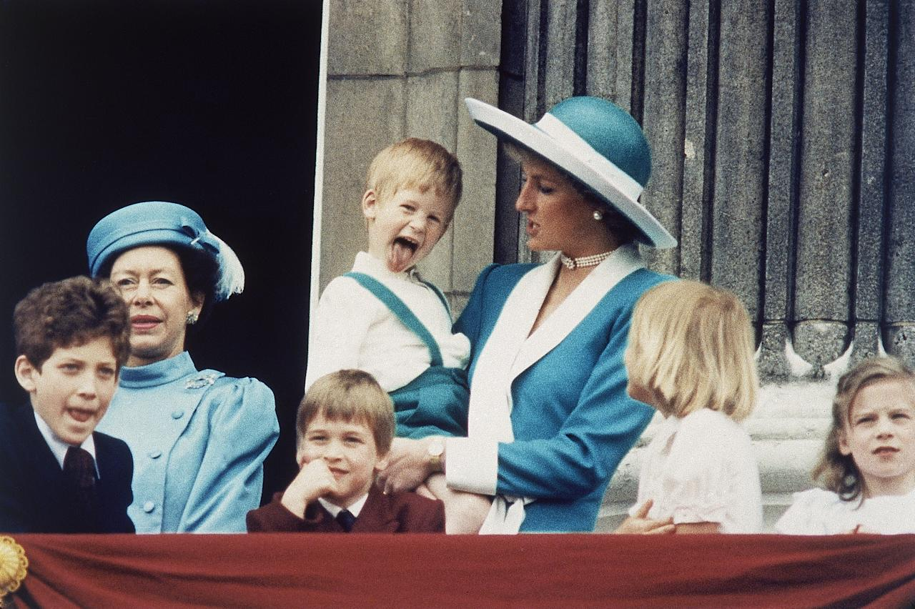 Britain's Prince Harry sticks out his tongue for the cameras on the balcony of Buckingham Palace in London, England on June 11, 1988, following the Trooping of the Colour. Princess Diana holds Harry, as a smiling Prince William sits in front, and Lady Gabriella Windsor is seen on the left. (AP Photo/Steve Holland)