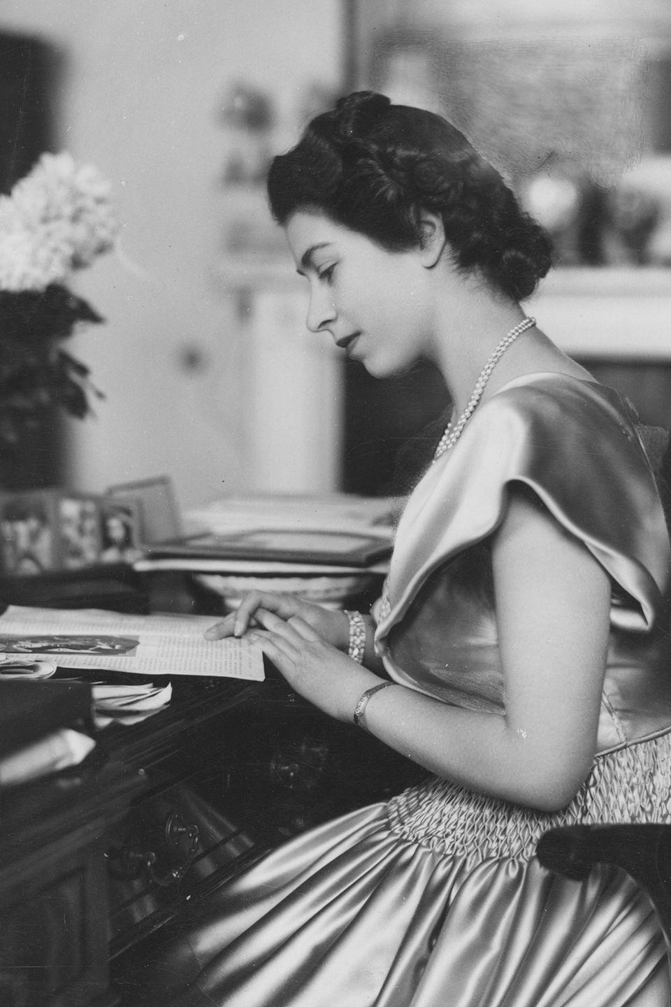 <p>A young Elizabeth sits at her desk in Buckingham Palace, possibly studying up on how to be a Queen.</p>