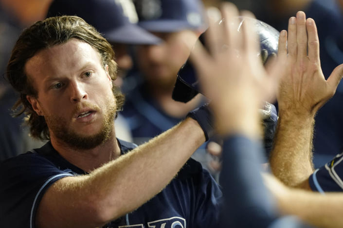 Tampa Bay Rays' Brett Phillips is congratulated after scoring in the seventh inning of the team's baseball game against the Cleveland Indians, Saturday, July 24, 2021, in Cleveland. (AP Photo/Tony Dejak)