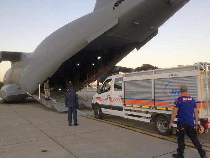 In this photo provided by Turkish Defense Ministry, rescue workers load goods into a cargo plane at a military airport near Ankara, Turkey, late Wednesday, Aug. 5, 2020. Turkey sent rescue teams and aid to Beirut after an explosion in the Lebanese capital's port killed more than 100 people and injured thousands on Tuesday. (Turkish Defense Ministry via AP, Pool)