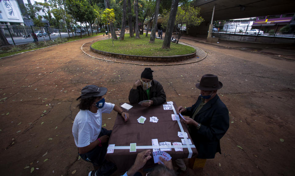 SAO PAULO, BRAZIL - MAY 07: Men wearing face masks playing cards in a square amidst the Coronavirus (COVID - 19) pandemic on May 7, 2020 in Sao Paulo, Brazil. The Government of the State of São Paulo has decreed the mandatory use of face masks in the streets. (Photo by Miguel Schincariol/Getty Images)