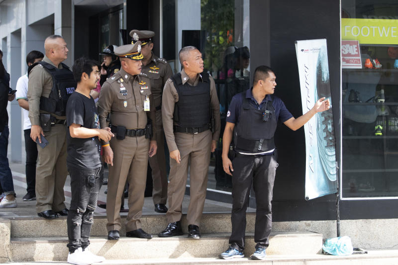 Thai police officers gather near the site of a shooting in Bangkok, Thailand, Friday, Feb. 14, 2020. Multiple gunshots have been fired into the air by a man in the middle of the capital Bangkok, police said.  (AP Photo/Sakchai Lalit)