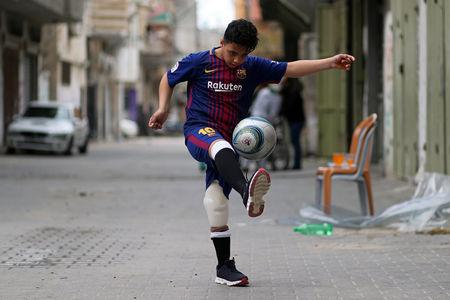 Palestinian boy Abdel-Rahman Nofal, 12, who, according to medics, lost his left leg after he was shot by Israeli forces during a protest at the Israel-Gaza border, plays soccer outside his house in the central Gaza Strip April 1, 2019. REUTERS/Mohammed Salem/Files