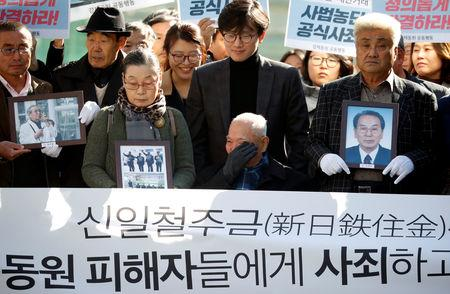 Lee Choon-shik, a victim of wartime forced labor during the Japanese colonial period, reacts as he arrives with supporters holding portraits of fellow deceased laborers in Seoul, South Korea, October 30, 2018.  REUTERS/Kim Hong-Ji