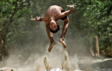 A boy somersaults as he practices diving on the banks of the Yamuna river on a hot summer day in New Delhi, India, April 22, 2016. REUTERS/Anindito Mukherjee