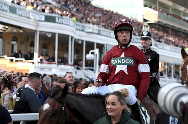 Jockey Davy Russell is led back to the parade ring after riding Tiger Roll to victory in the Grand National horse race at Aintree Racecourse in Liverpool, northern England on April 14, 2018 (AFP Photo/Jason ROBERTS)