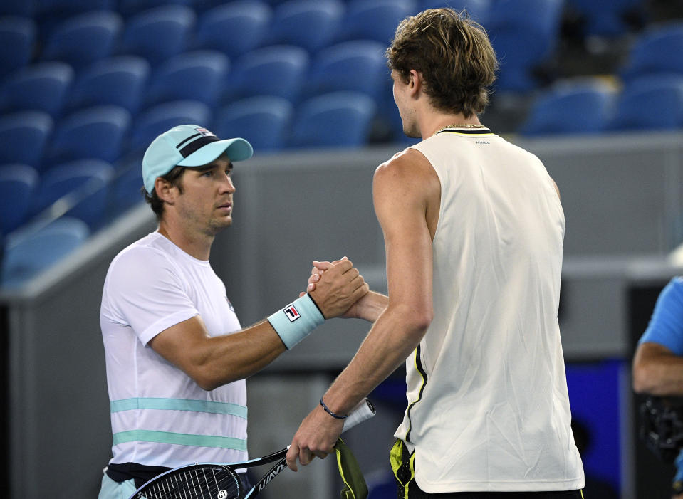 Germany's Alexander Zverev, right, and Serbia's Dusan Lajovic shake hands after Zverev won their fourth round match at the Australian Open tennis championships in Melbourne, Australia, Sunday, Feb. 14, 2021. (AP Photo/Andy Brownbill)