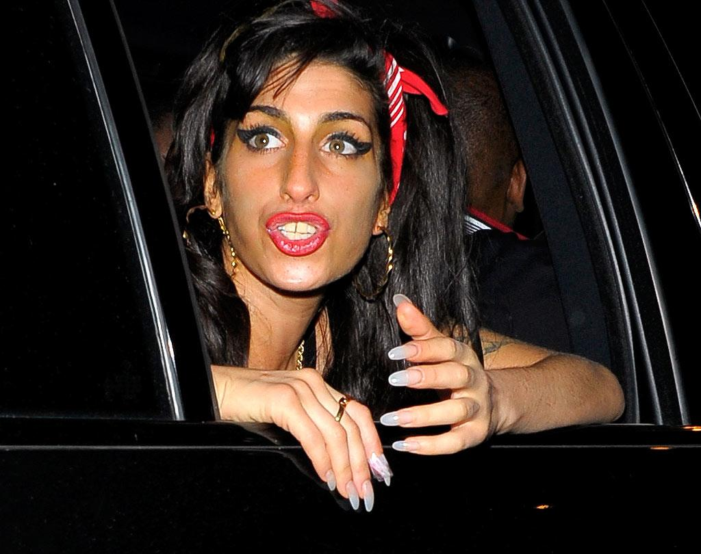 """Sporting a tan Snooki would be proud to own, a headscarf that matched her lips, and super scary nails, troubled singer Amy Winehouse was spotted leaving London's 100 Club Tuesday night. <a href=""""http://www.splashnewsonline.com"""" target=""""new"""">Splash News</a> - July 6, 2010"""