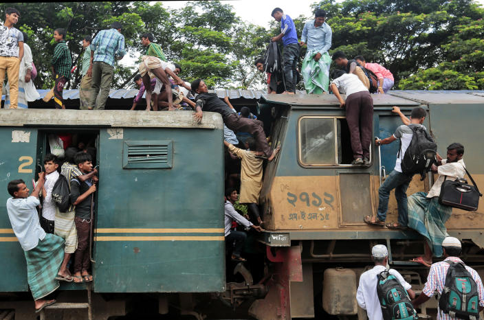 <p>Bangladeshi passengers try to climb on to the roof of an overcrowded train as they head home ahead of Eid al-Fitr at a railway station in Dhaka, Bangladesh, July 1, 2016. (Photo: A.M. Ahad/AP) </p>