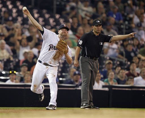 San Diego Padres third baseman Chase Headley, left, throws out Colorado Rockies' Wilin Rosario, on a ground ball with third base umpire Manny Gonzalez, right, signals a fair ball during the fourth inning of their baseball game in San Diego, Calif., Friday, Sept. 14, 2012. (AP Photo/Alex Gallardo)