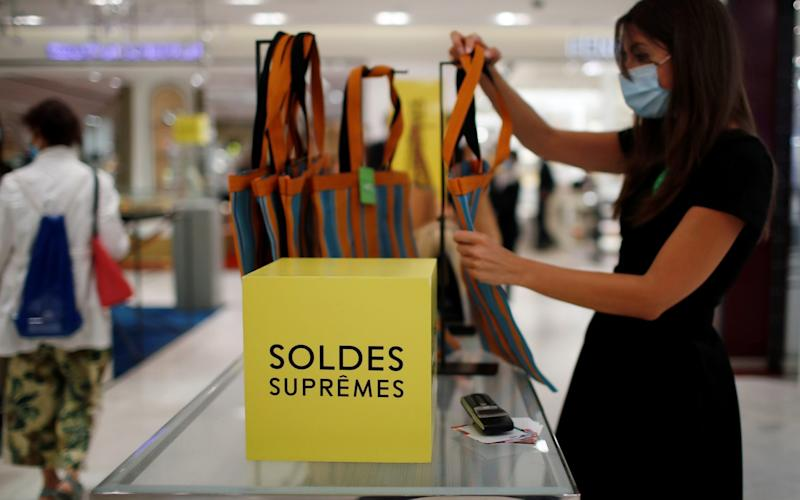 An employee, wearing a protective face mask, checks bags with discount signs at the department store Le Printemps Haussmann in Paris - GONZALO FUENTES/Reuters