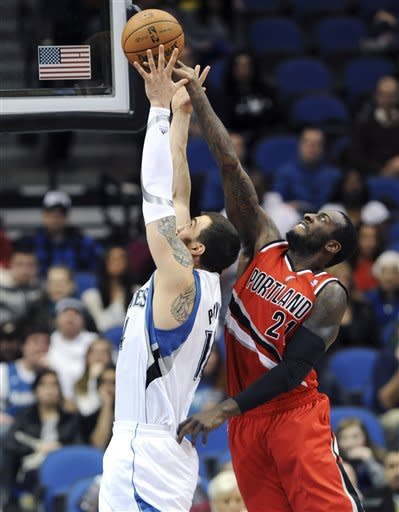 Minnesota Timberwolves' Nikola Pekovic, left, of Montenegro, and Portland Trail Blazers' J.J. Hickson battle for the rebound in the first quarter of an NBA basketball game, Saturday, Jan. 5, 2013, in Minneapolis. (AP Photo/Jim Mone)