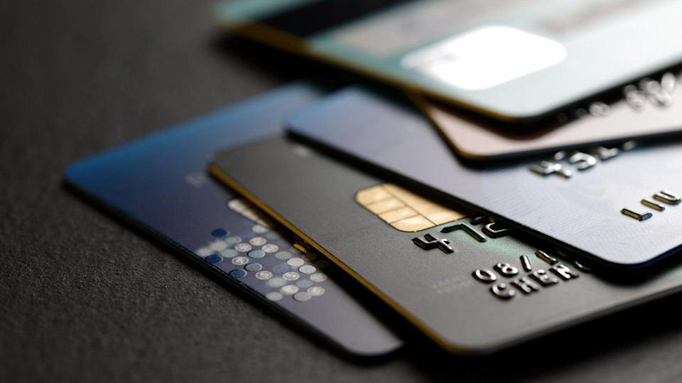 stack of multicolored credit cards on black background.