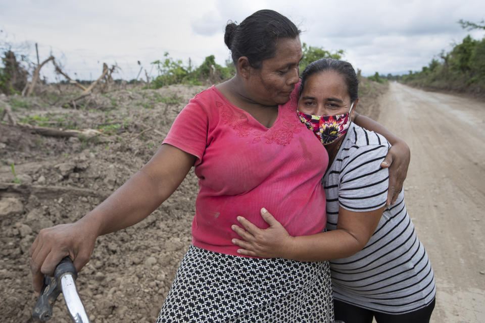 Xiomara Cruz, right, and Melinda Martínez reunite for the first time since last year's hurricanes Eta and Iota on the route to a banana plantation where they worked before last year's storms destroyed the area in La Lima, on the outskirts of San Pedro Sula, Honduras, Wednesday, Jan. 13, 2021. The devastation wrought by November's hurricanes and the economic damage of the COVID-19 pandemic has added to the forces of poverty and gang violence that drive Hondurans to migrate. (AP Photo/Moises Castillo)