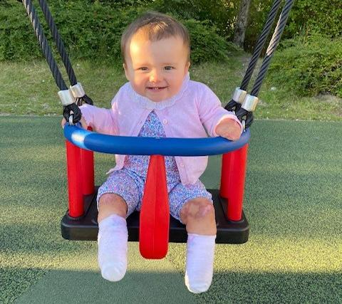 Phoebe Moon is pictured in a baby swing after her surgery where her feet and fingers were amputated.