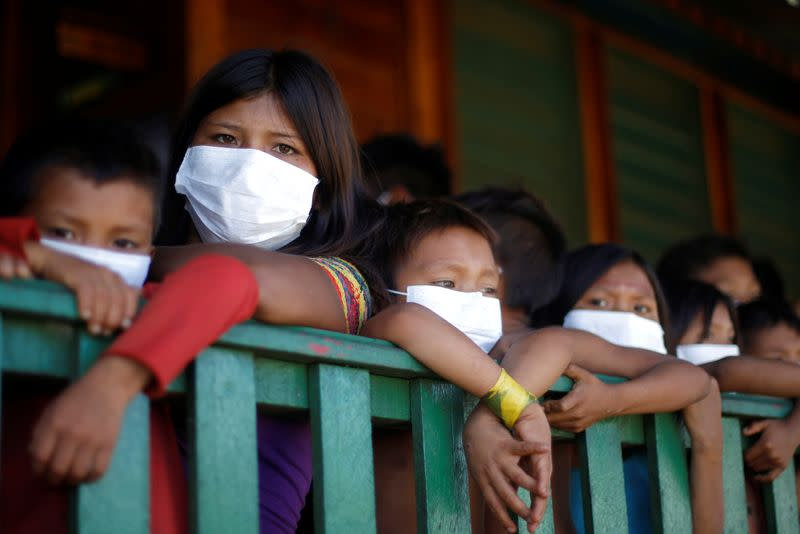 Children from the indigenous Yanomami ethnic group wearing protective face mask look on, amid the spread of the coronavirus disease (COVID-19), at the 5th Special Frontier Platoon in the municipality of Auaris