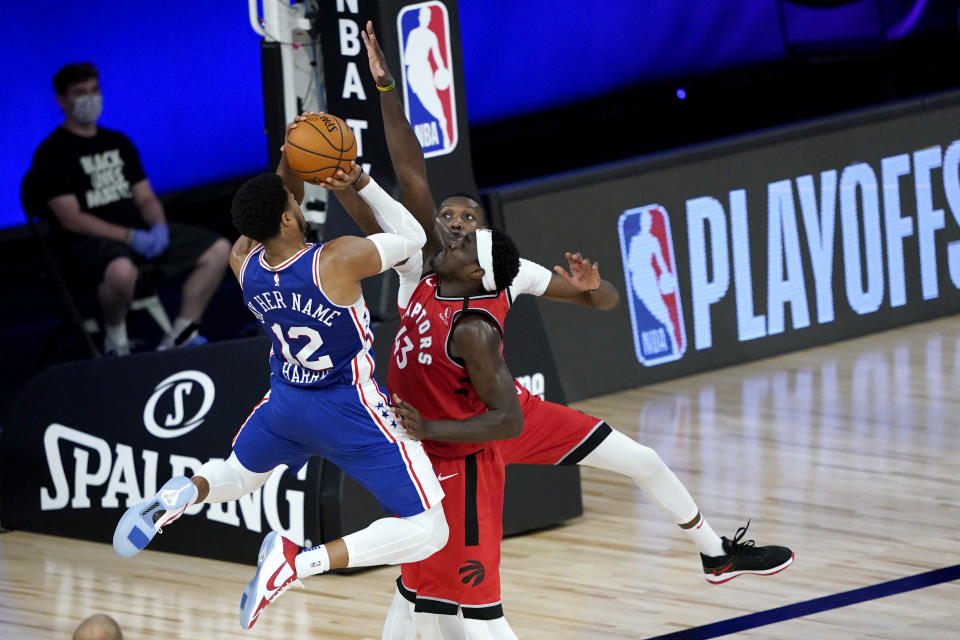 Philadelphia 76ers' Tobias Harris (12) goes up for a shot against Toronto Raptors' Pascal Siakam, center, and Chris Boucher during the first half of an NBA basketball game Wednesday, Aug. 12, 2020 in Lake Buena Vista, Fla. (AP Photo/Ashley Landis, Pool)