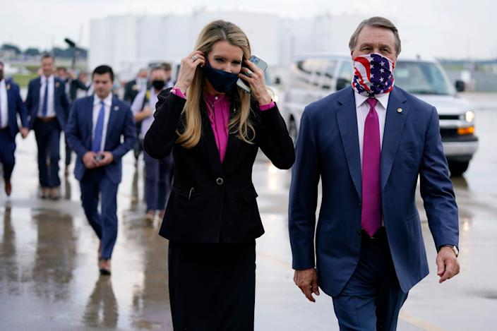In this July 15 file photo Sen. Kelly Loeffler, R-Ga., puts on a face mask as she walks with Sen. David Perdue, R-Ga., right, at UPS Hapeville Airport Hub in Atlanta.