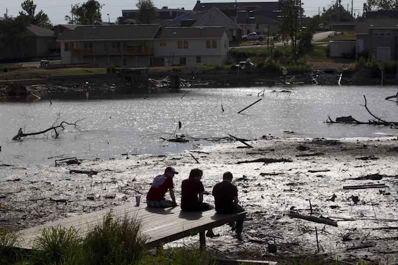Kevin Gloda, left, of Baton Rouge, La., Robert McCray of Tuscaloosa and Aaron Fleshner, right, of Spring, Texas, sit on a dock to reflect at Forest Lake in Tuscaloosa, Ala., Friday, April 27, 2012. Fifty-three people were killed a year ago in Tuscaloosa and 253 people were killed when 62 tornadoes struck the state a year ago. (AP Photo/Dave Martin)