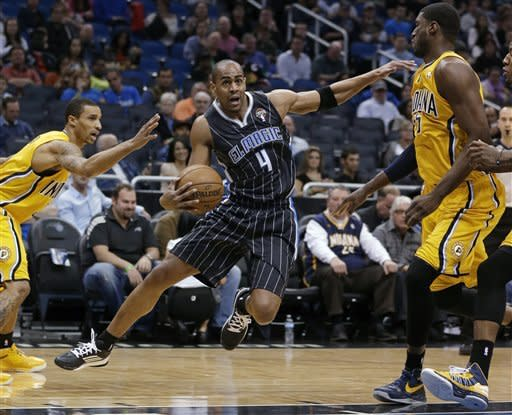 Orlando Magic's Arron Afflalo (4) drives to the basket between Indiana Pacers' David West, left, and Roy Hibbert during the first half of an NBA basketball game, Friday, March 8, 2013, in Orlando, Fla. (AP Photo/John Raoux)
