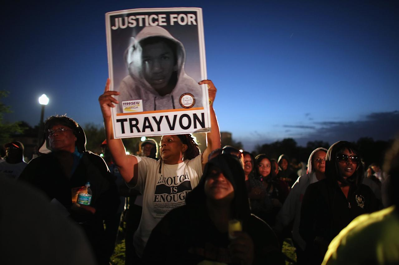 SANFORD, FL - FEBRUARY 26: Debra (who didn't want to use her last name) stands with a sign as she and others hold a vigil at Fort Mellon Park to mark the one year anniversary of when Trayvon Martin was killed on February 26, 2013 in Sanford, Florida. Martin was shot by George Zimmerman while Zimmerman was on neighborhood watch patrol in the gated community of The Retreat at Twin Lakes in Sanford, Florida.  (Photo by Joe Raedle/Getty Images)