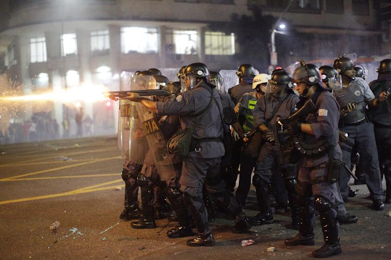 Police fire rubber bullets at demonstrators protesting a price increase for public transportation in Sao Paulo, Brazil, Thursday, June 13, 2013. Thousands of protesters are taking to the streets in Brazil's two biggest cities, protesting against 10-cent hikes in bus and subway fares. (AP Photo/Nelson Antoine)