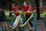 A woman wearing a face mask to protect against COVID-19 uses an exercise machine at a public park in Beijing, Thursday, Sept. 9, 2021. (AP Photo/Mark Schiefelbein)