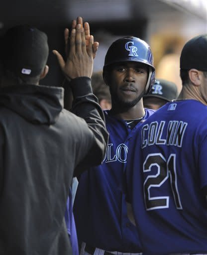 Colorado Rockies' Dexter Fowler is congratulated by teammates in the dugout after scoring on a Jordan Pacheco RBI single against the Miami Marlins during the fourth inning of a baseball game in Denver, Friday, Aug. 17, 2012. (AP Photo/Jack Dempsey)