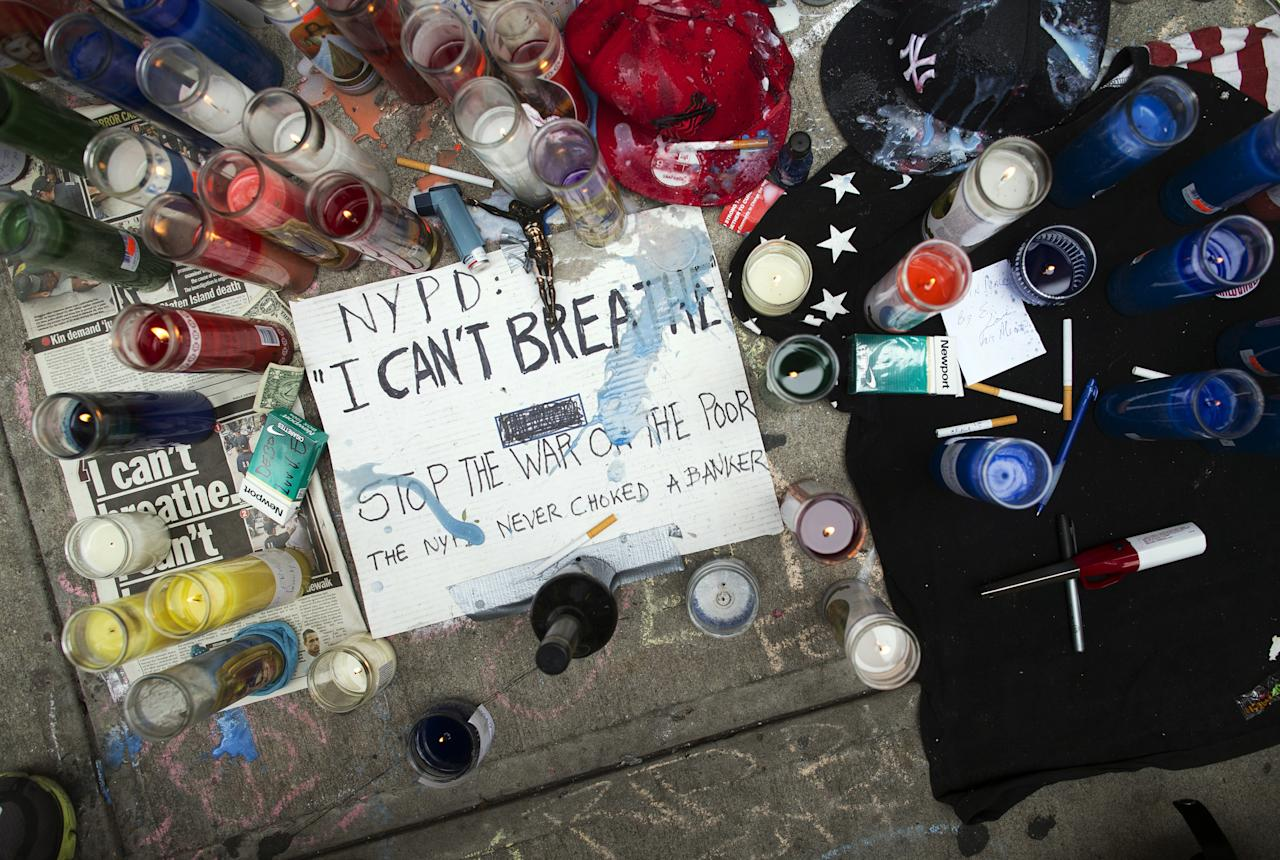 FILE - This July 19, 2014 file photo shows a memorial for Eric Garner on the pavement near the site of his death when taken into custody by police, in the Staten Island borough of New York. Three years after Garner's chokehold death the wheels of justice are turning more slowly than in similar cases. Federal prosecutors have said privately that a decision about whether to charge the police officer seen on video wrapping his arm around Garner's neck is still months away, frustrating the victim's family and leaving the officer's career in limbo. (AP Photo/John Minchillo, File)