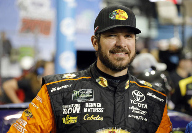 Martin Truex Jr. stands next to his car during qualifying for the NASCAR Cup Series auto race at the Homestead-Miami Speedway, Friday, Nov. 16, 2018, in Homestead, Fla. (AP Photo/Terry Renna)