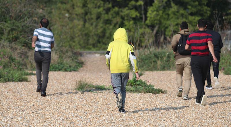 A group of people thought to be migrants run across Kingsdown beach, near Dover, Kent, where they arrived after crossing the English Channel.