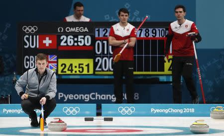 Curling - Pyeongchang 2018 Winter Olympics - Men's Tie-Breaker - Switzerland v Britain - Gangneung Curling Center - Gangneung, South Korea - February 22, 2018 - Thomas Muirhead of Britain indicates a play as Benoit Schwarz, Claudio Patz and Peter de Cruz of Switzerland watch. REUTERS/Cathal McNaughton