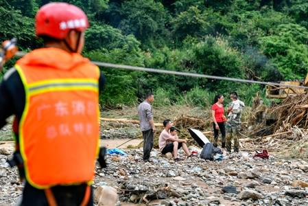 Rescue workers help evacuate stranded villagers affected by flood following heavy rainfall in Heyuan