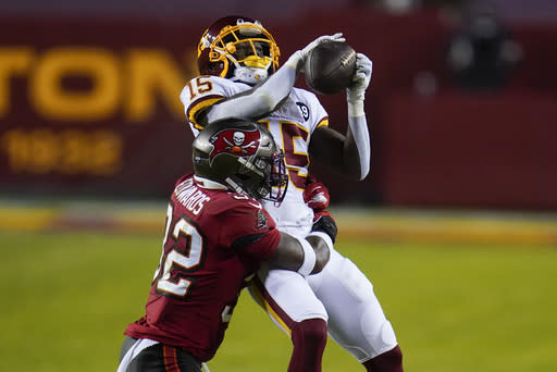 Washington Football Team wide receiver Steven Sims (15) makes a catch against Tampa Bay Buccaneers safety Mike Edwards (32) during the first half of an NFL wild-card playoff football game, Saturday, Jan. 9, 2021, in Landover, Md. (AP Photo/Julio Cortez)