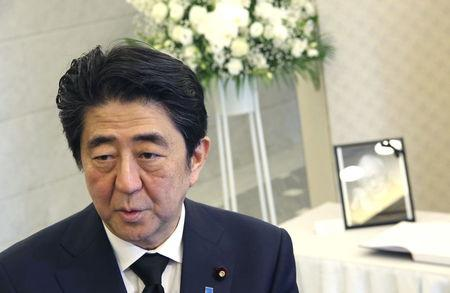 Japan's Prime Minister Shinzo Abe speaks to the media after signing a condolences book for the late Lee Kuan Yew, former Prime Minister of Singapore, at the Singapore Embassy in Tokyo