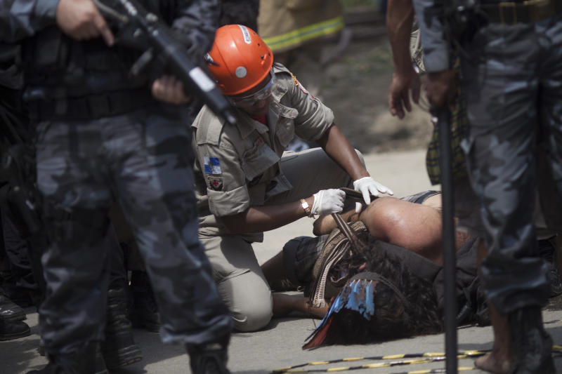 An Indian man laying on the ground receives medical attention after being evicted from the old Indian Museum in Rio de Janeiro, Friday, March 22, 2013. Police in riot gear invaded an old Indian museum complex Friday and pulled out a few dozen indigenous people who for months resisted eviction from the building, which will be razed as part of World Cup preparations next to the legendary Maracana football stadium. (AP Photo/Felipe Dana)