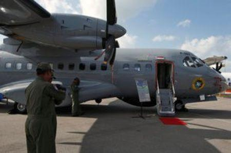 Indonesian airforce personnel stand next to their CN235-220 maritime surveillance aircraft displayed at the Singapore Airshow at Changi Exhibition Center February 17, 2016. Picture taken February 17, 2016. REUTERS/Edgar Su