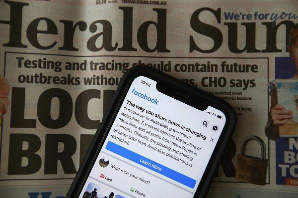 An iPhone is placed on a copy of the Herald Sun with Facebook open.