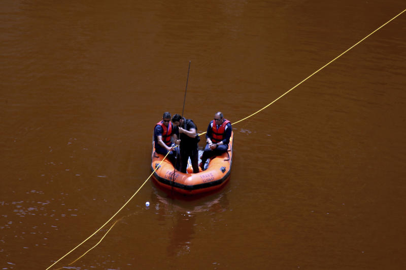 Members of the Cyprus Special Disaster Response Unit are seen in boat as they search for suitcases in a man-made lake, near the village of Mitsero outside of the capital Nicosia, Cyprus, Tuesday, April 30, 2019. Cyprus police spokesman Andreas Angelides says British experts called in to assist in the east Mediterranean island nation's serial killer case have been brought up to speed on the ongoing probe. (AP Photo/Petros Karadjias)